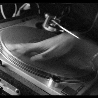 A photo of a DJ spinning a record in mid spin, such that the hand on the record is blurred.