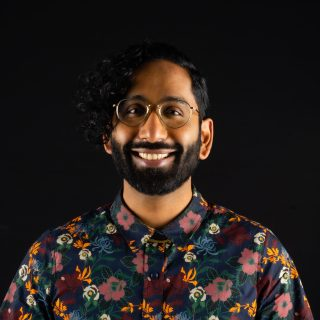A headshot for Imran Siddiquee, shown smiling and wearing a floral print shirt.