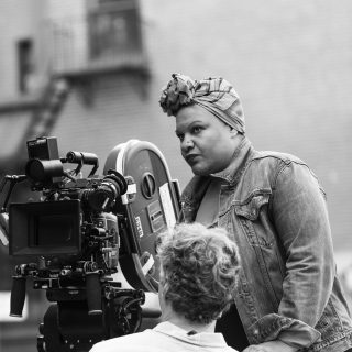 Photo of Radha Blank, standing behind a film camera, directing