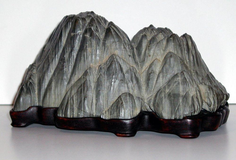 batu seni suiseki dipajang di atas tatakan kayu