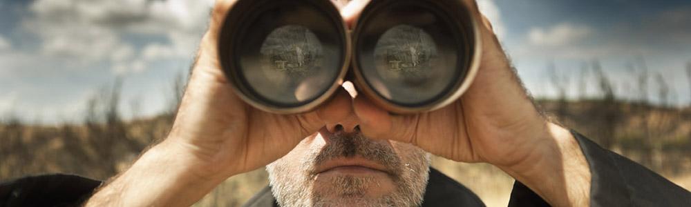Man with binoculars in a field