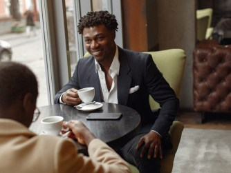 Black men sitting in a cafe drinking coffee