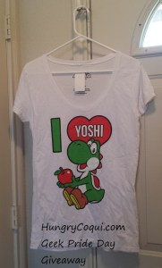 This ladies tee features Yoshi and is a generously cut size medium. I have one that fits comfortably and I normally wear a large. Two of these will be given away.