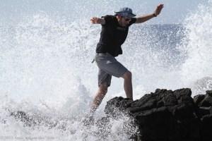 Pedro runs from the crashing waves at South Point, HI