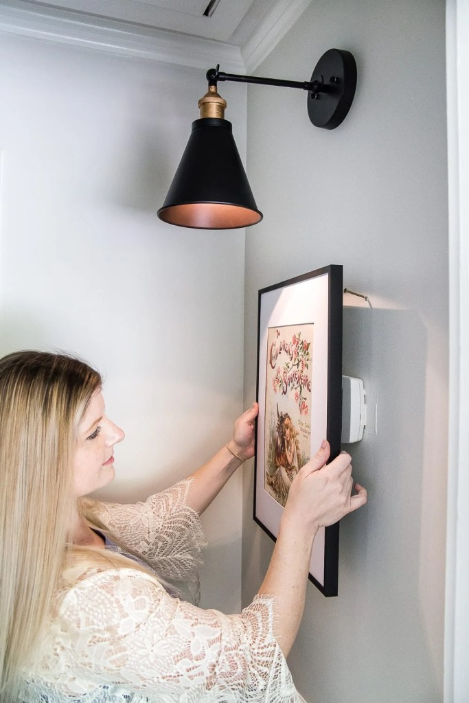 Simple Thermostat Cover and Hallway Progress | A dark, beige hallway gets a light and bright makeover, plus a solution for creating an inexpensive thermostat cover and sconce lighting without the electrical work. #thermostatcover #hallway #hallwaymakeover #beforeandafter #sconce #sconcelight #walldecor #wallart #budgetdecor #freeart #decortrick #eyesorecover Simple Thermostat Cover