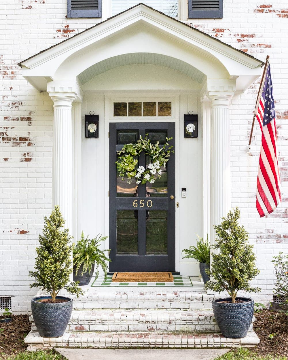 A house exterior makeover update with landscaping changes, new porch lights, and decor for summer to make an inviting, bright entrance. #porch #summerdecor #landscaping #summerporch #porchlights #outdoorlighting #limewashing #limewashedbrick #brickexterior #summerhouse #colonial #colonialhouse