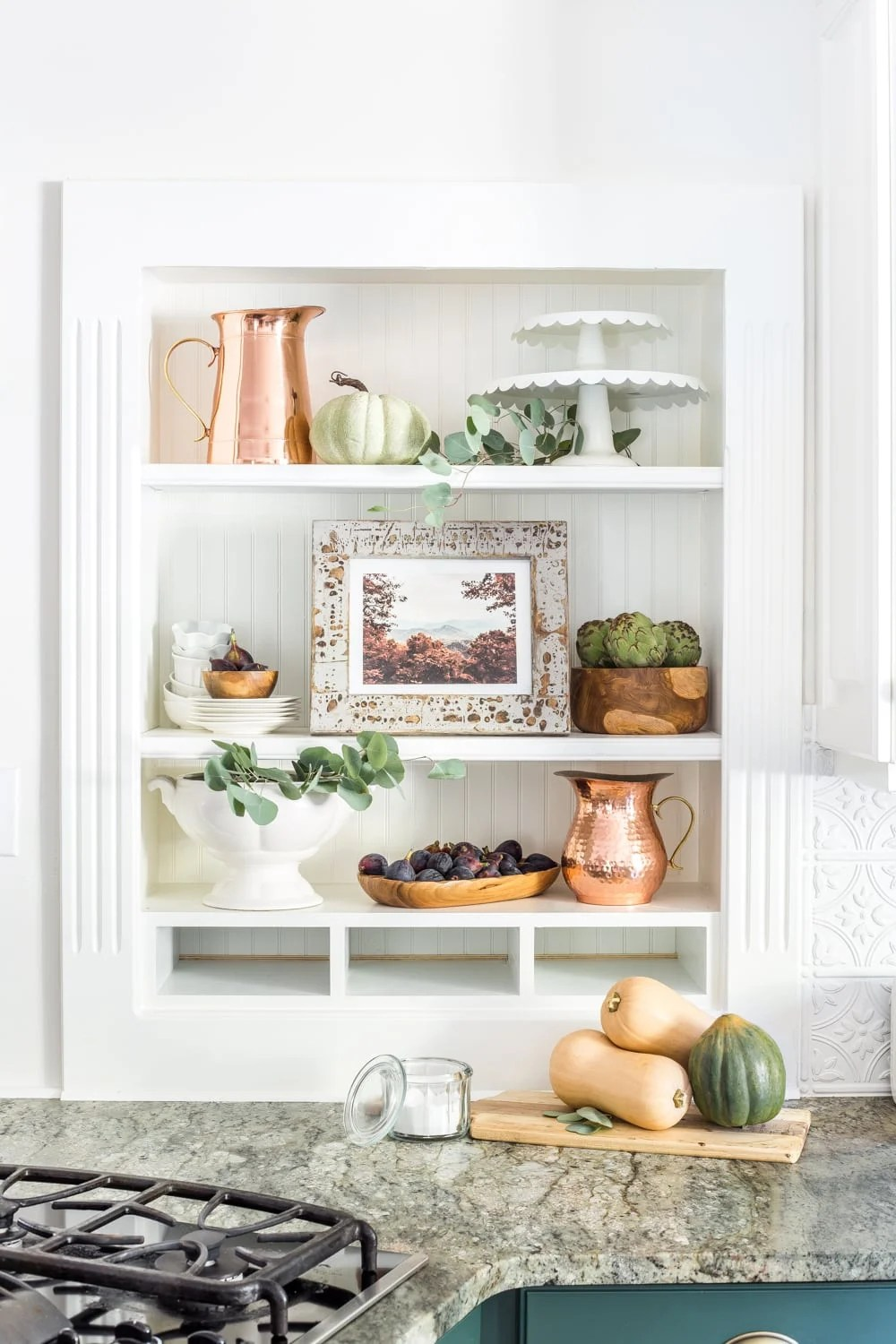 kitchen shelves decorated for fall with framed art and copper pitchers and pumpkins