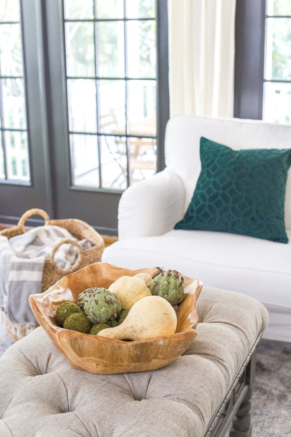 wooden bowl of gourds and artichokes on a living room coffee table