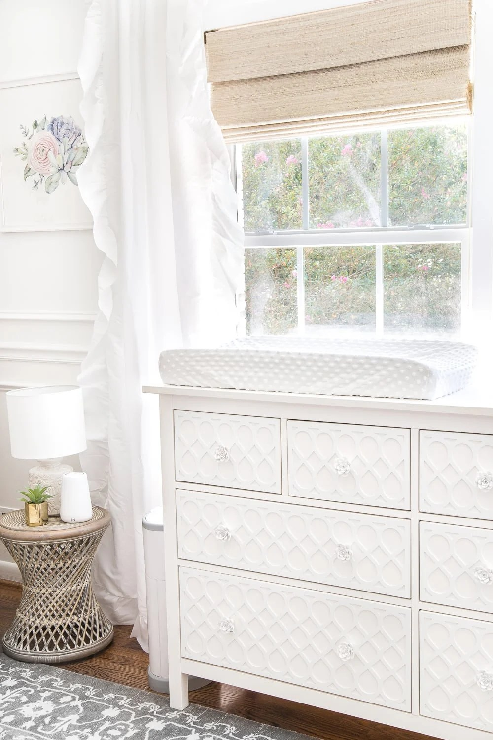 An all white nursery makeover room reveal with classic, vintage style furniture, Anthropologie-inspired patterns and textures, and floral accents.