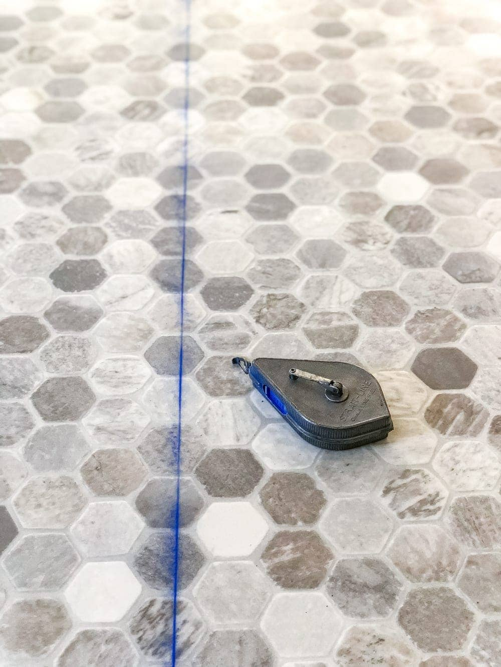 How to install sheet vinyl flooring over old tile | Use a chalk line to cut straight lines between measurements