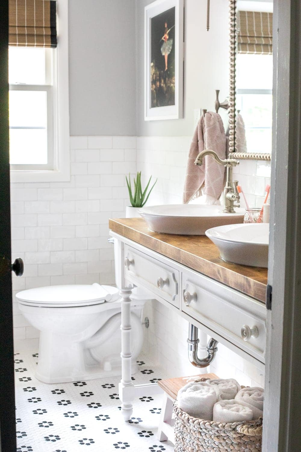 Girls' Bathroom Decor Details & Sources | Console table converted into a vanity with vessel sinks and retro flower floor tile