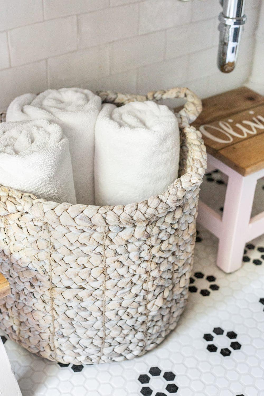 Girls' Bathroom Decor Details & Sources | basket of towels underneath an open vanity table