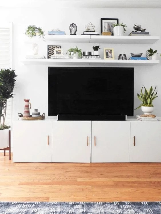 Add floating shelves above a TV for a built-in look on the cheap.