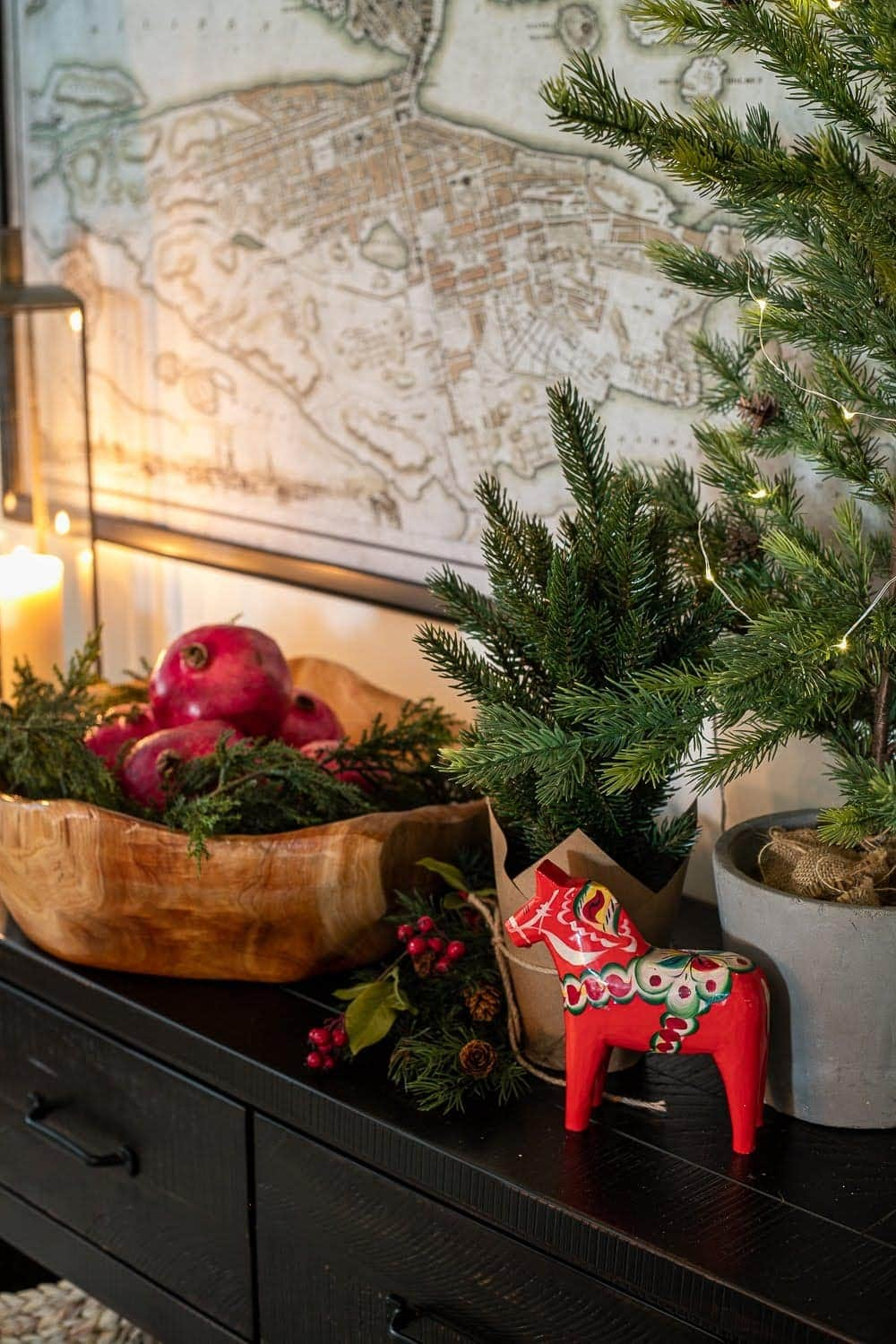 Swedish Christmas vignette with candlelight, Dala horse, bowl of pomegranates, greenery, and twinkle lights for hygge