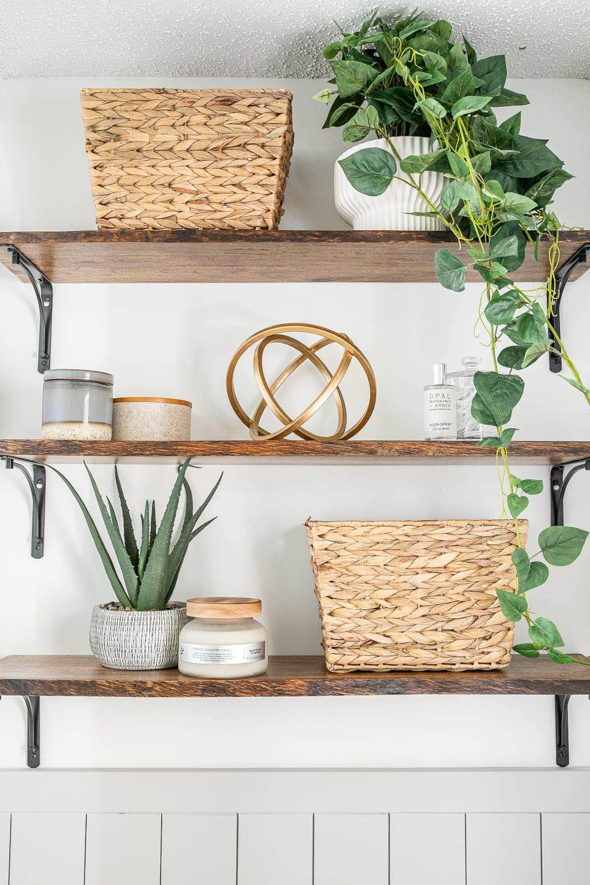 bathroom shelves with baskets, small storage, plants, and decor