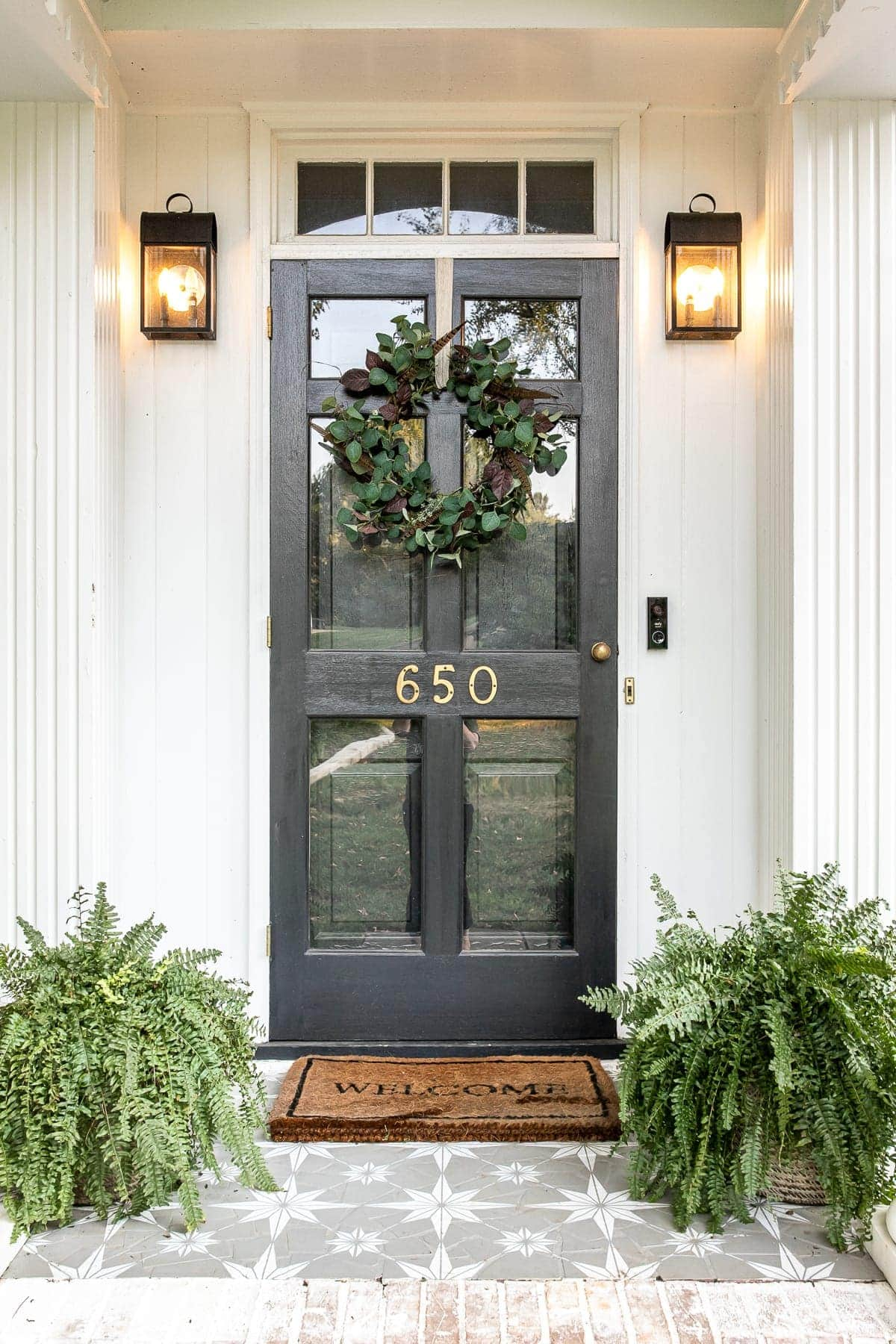 Front porch decorated for early fall with DIY wreath and stenciled floor