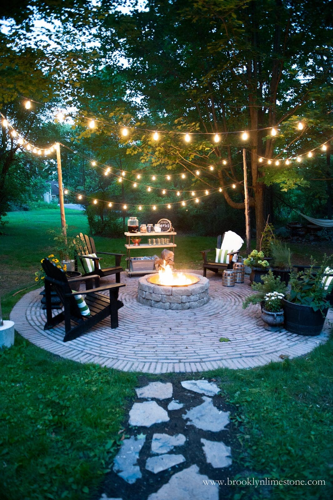fire pit with string lights and stone walkway