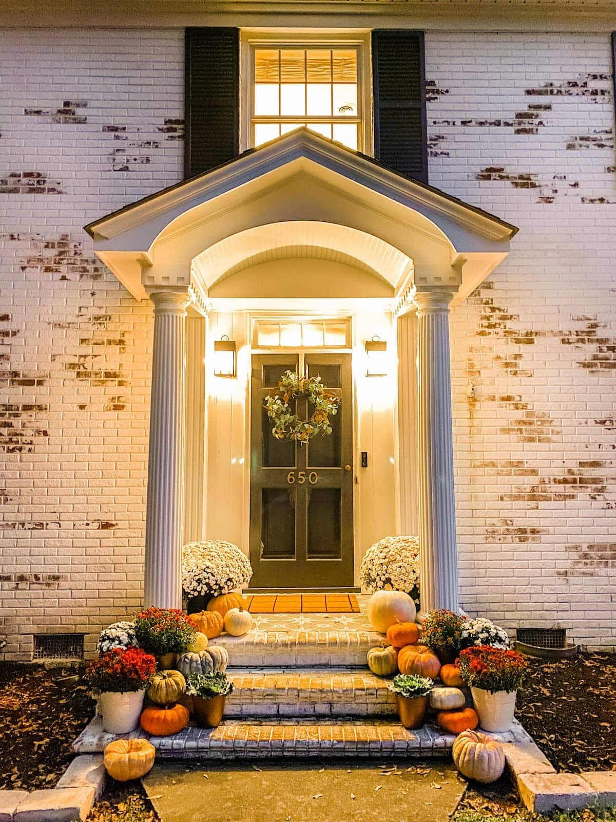 fall porch at night with pumpkins and mums and limewashed brick