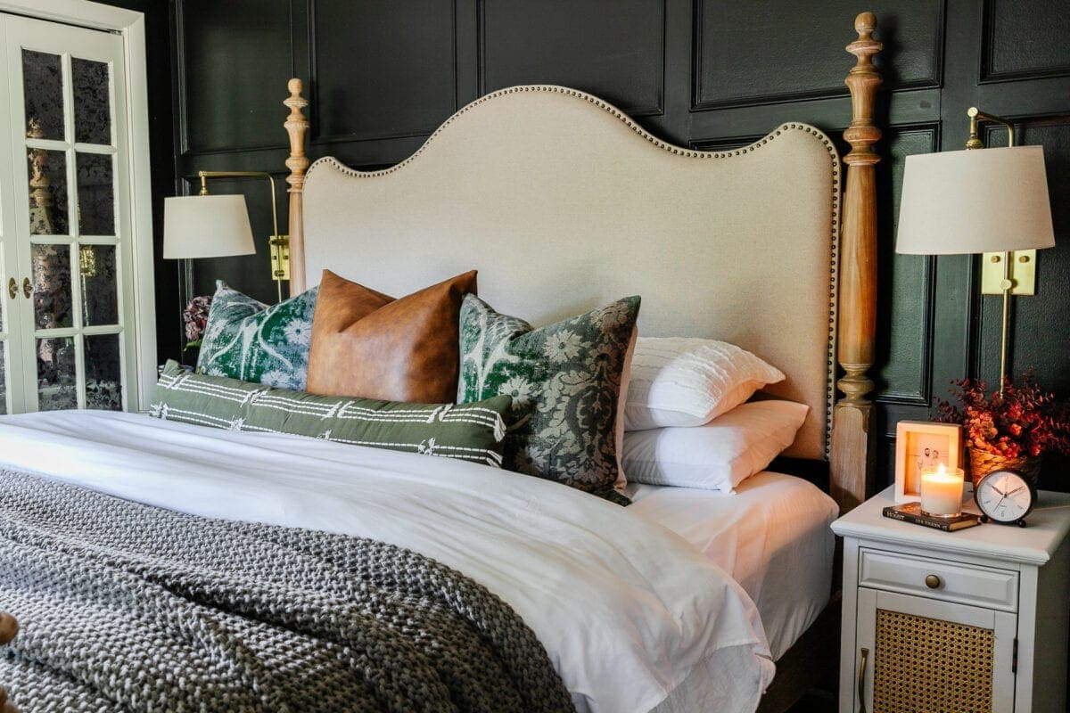 throw pillows on a bed with black walls and linen headboard