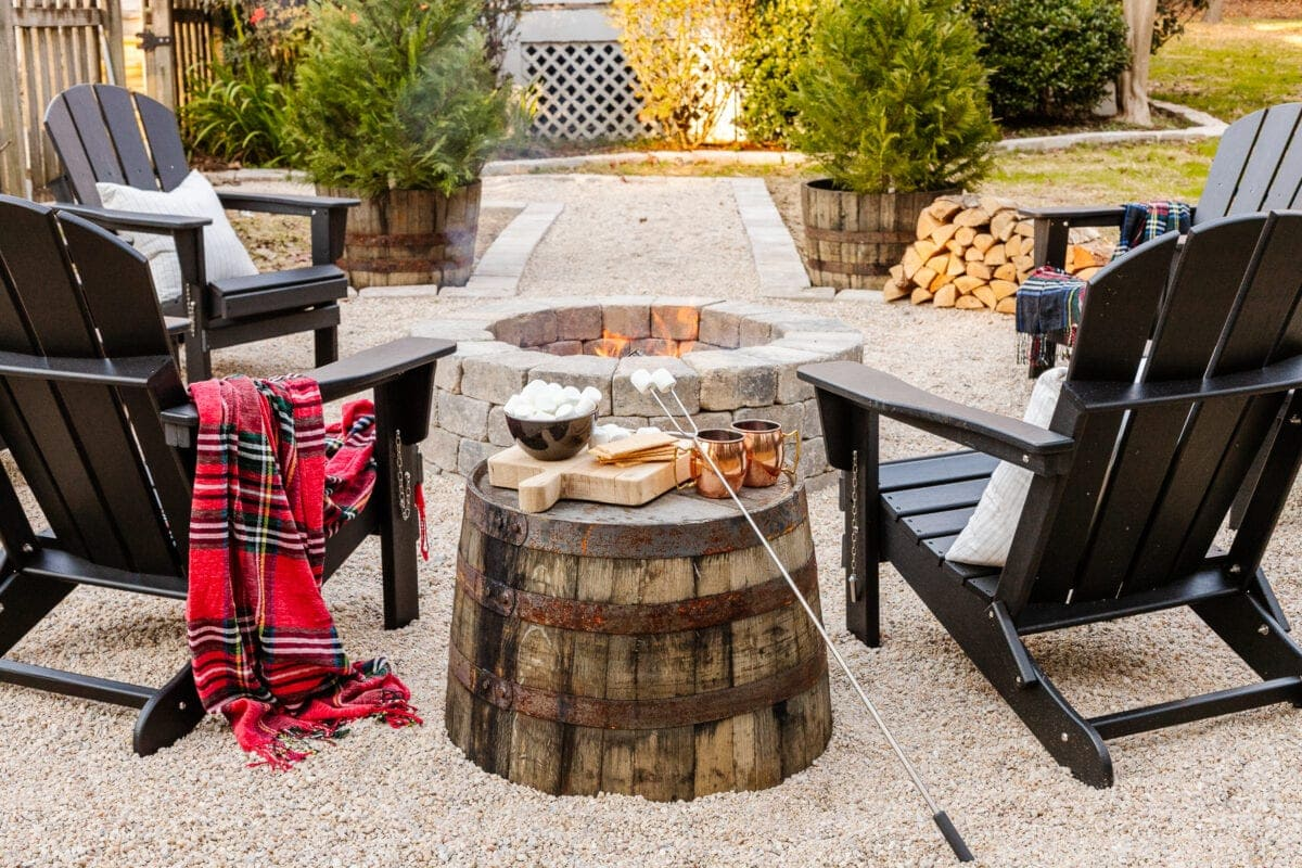stone fire pit with pea gravel, stone edgers, and adirondack chairs with a barrel planter as a side table