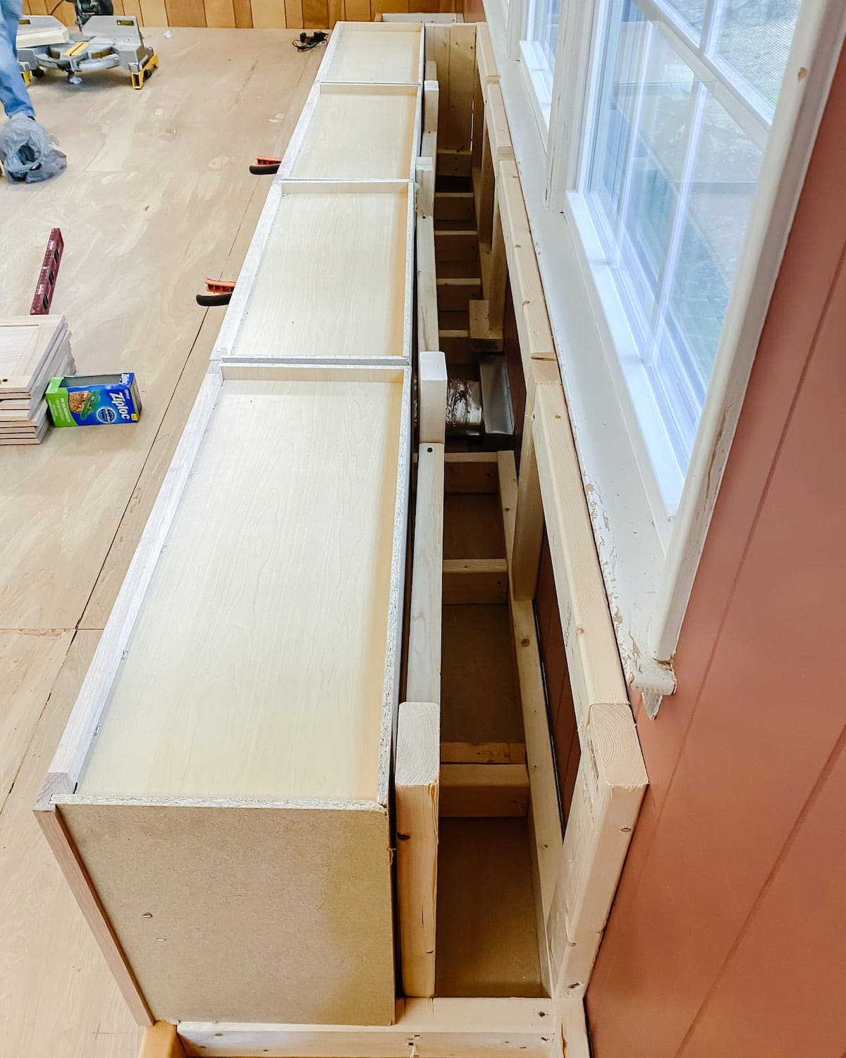 A step-by-step tutorial to build DIY built in cabinets and a window seat using inexpensive stock kitchen cabinets.