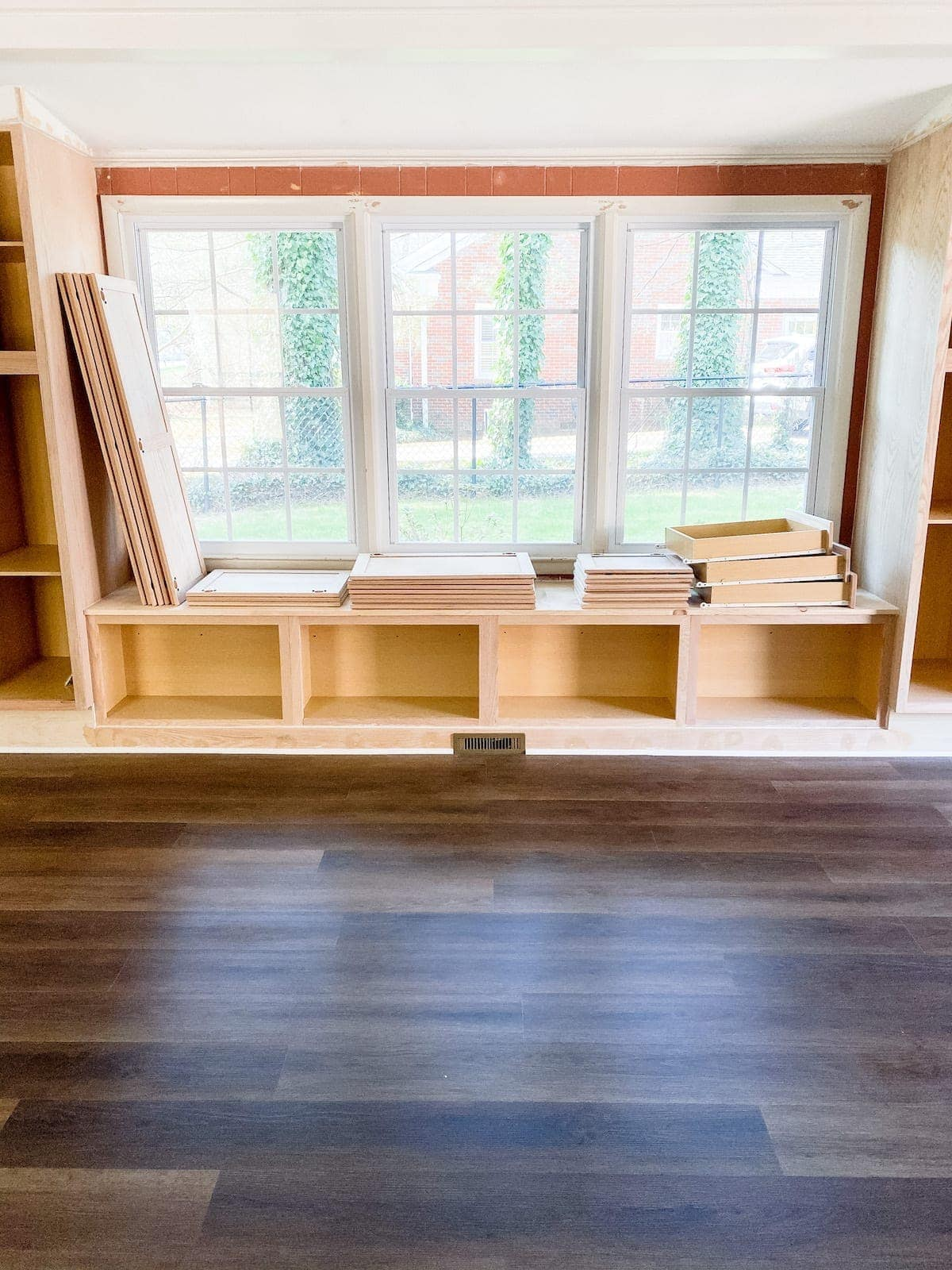luxury vinyl plank flooring with DIY built-in cabinets and window seat
