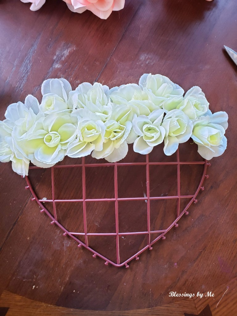 Add the cream flowers to the top of the Valentine's heart wreath