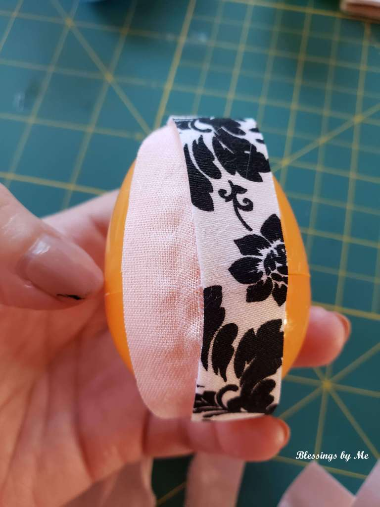 glue the fabric scraps to the plastic egg
