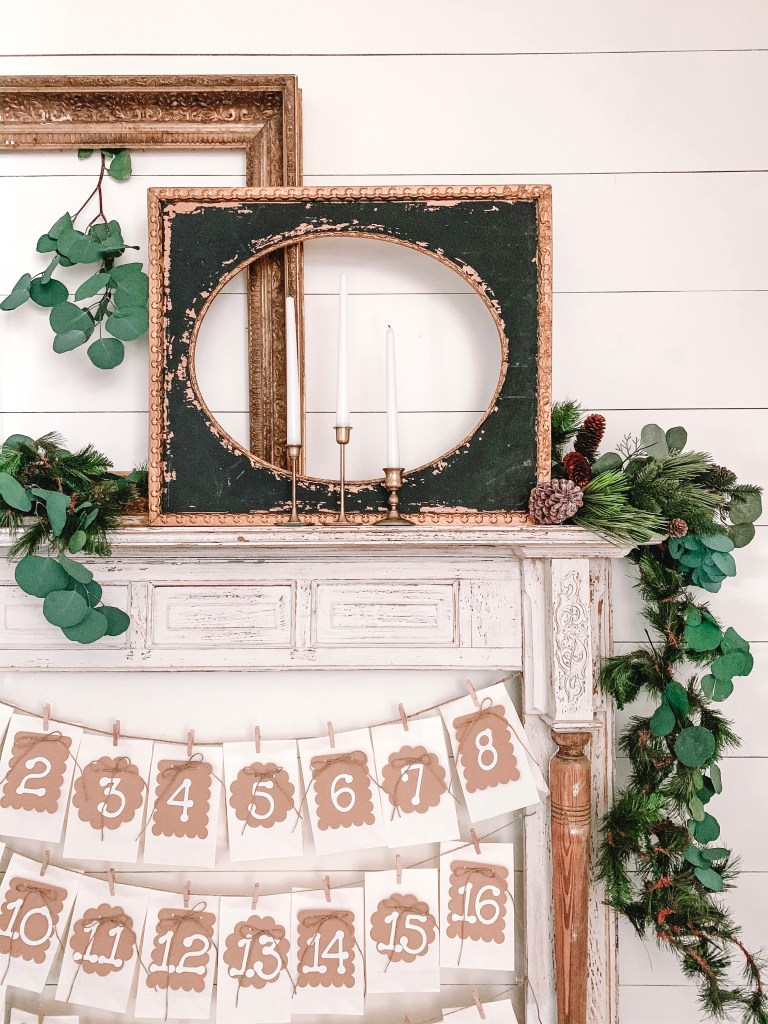 Black and gold frames and garland on faux mantel.