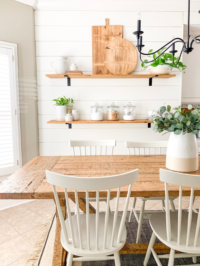 white shiplap wall with wood shelves in kitchen eating nook