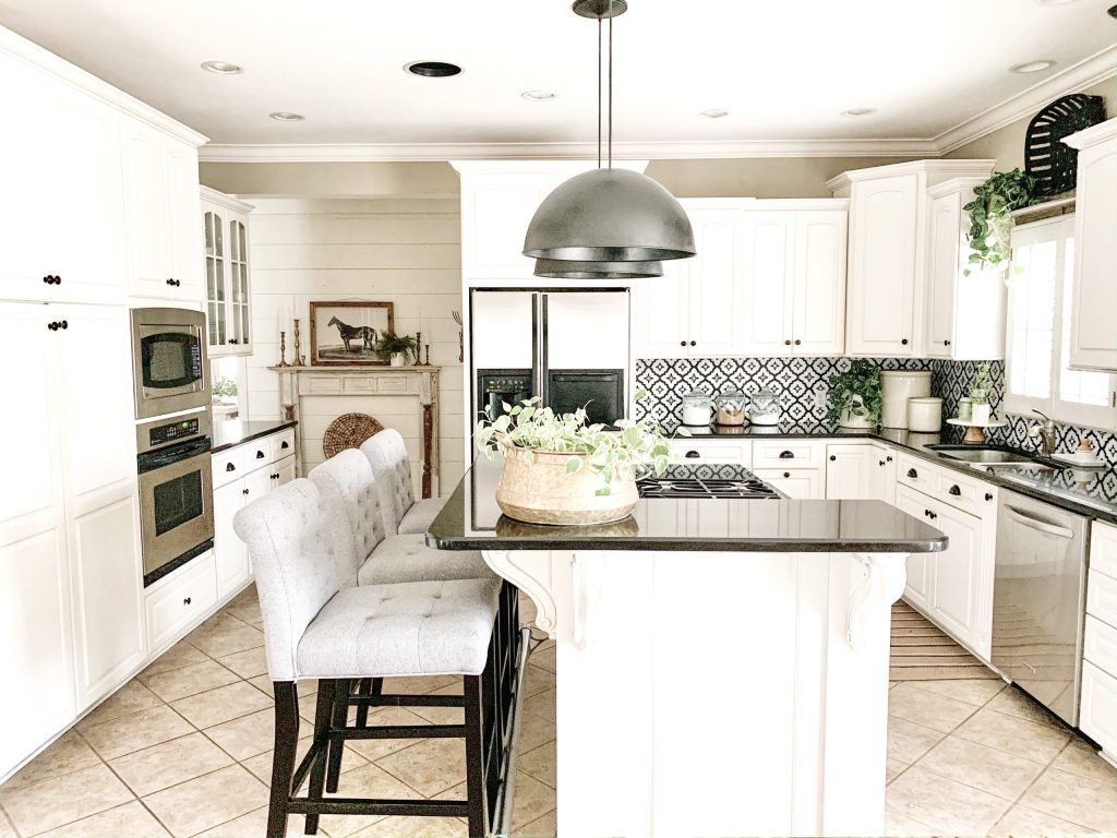 white kitchen reveal with black dome pendants over island.