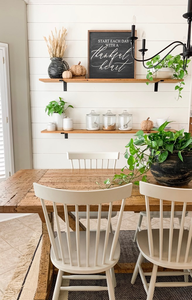 farm table with plant centerpiece and white chairs