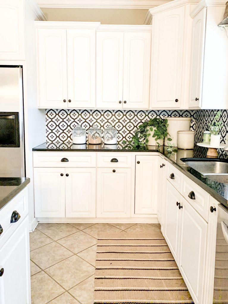 white kitchen with black and white pattern backsplash