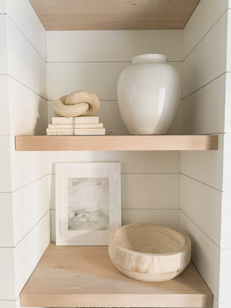 vase, books, picture, and bowl on shelves