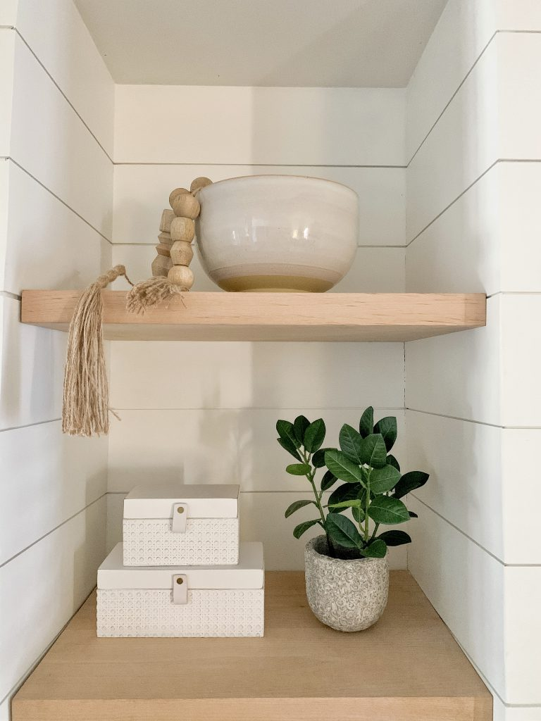 bowl with beads, layered boxes, and a plant on shelves