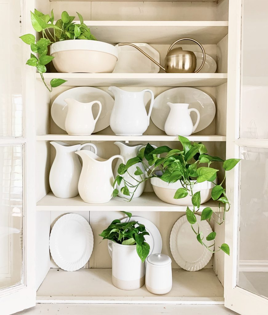 collection of pitchers, plates, and plants in white hutch