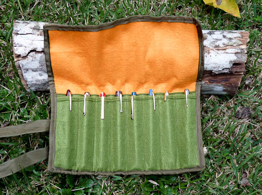An orange and green felt pen wrap with pens in it.