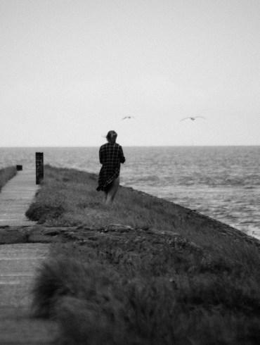 Vrouw op de dam bij de haven van West-Terschelling.