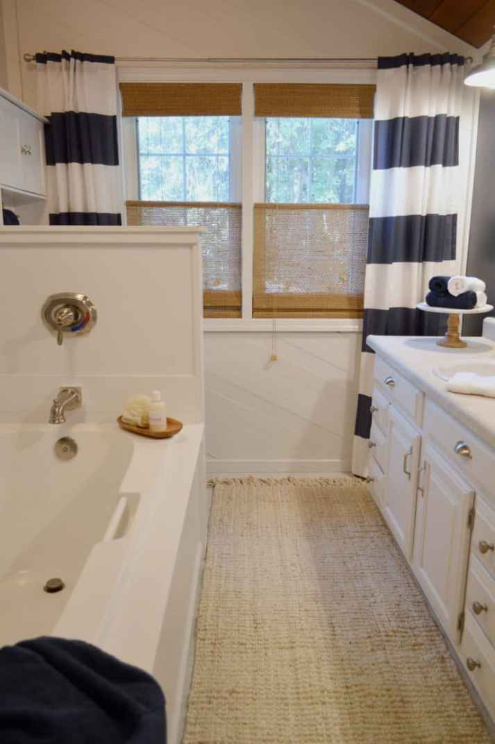 nautical bathroom with brown bamboo blinds and striped navy and white curtains