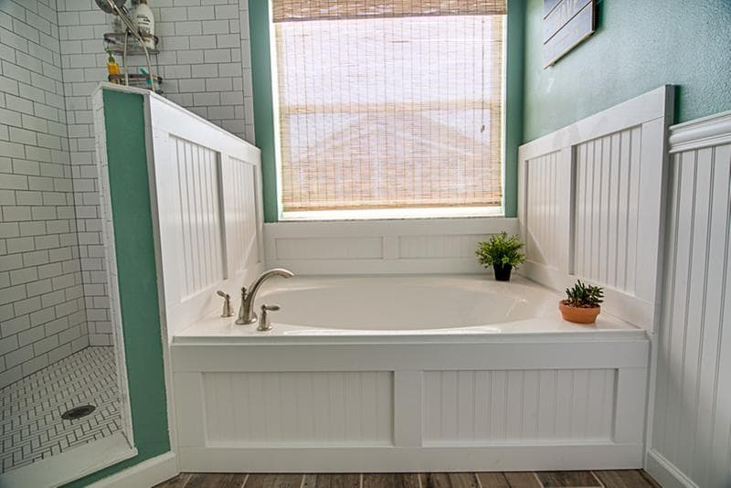 Green And White Bathroom With Subway Tile, Beadboard Walls And Bamboo Shade  Over Bathtub