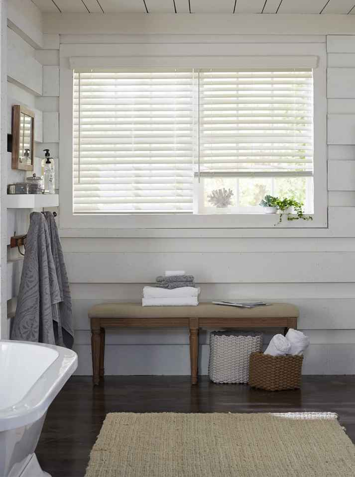 bathroom with wood walls painted white and window with two white wood blinds