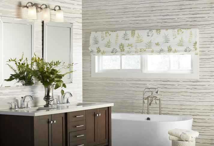 bathroom window covered with roman shades with green botanical fern print