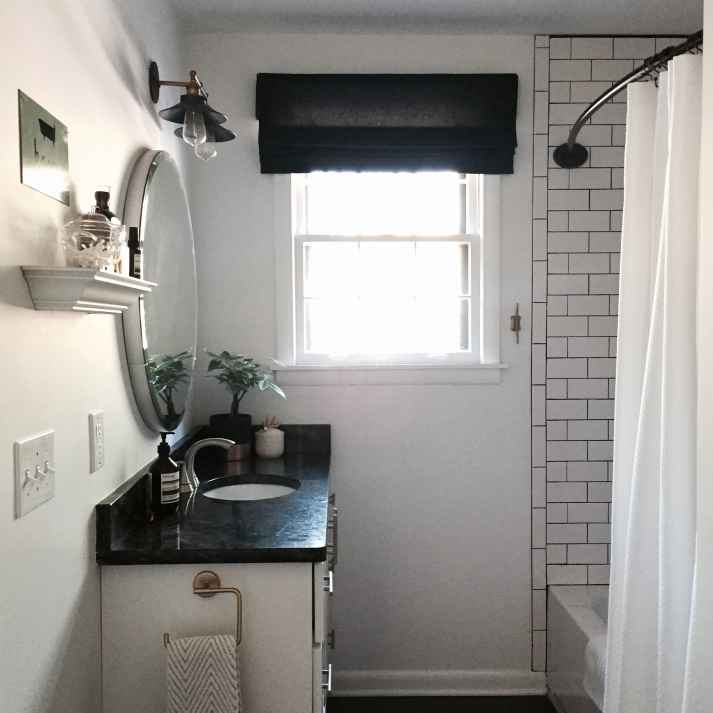 black and white bathroom with black roman shade on window