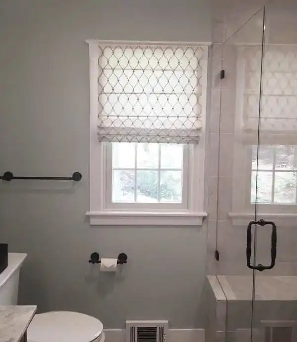 traditional bathroom with small window covered with white roman shades with embroidered trellis pattern