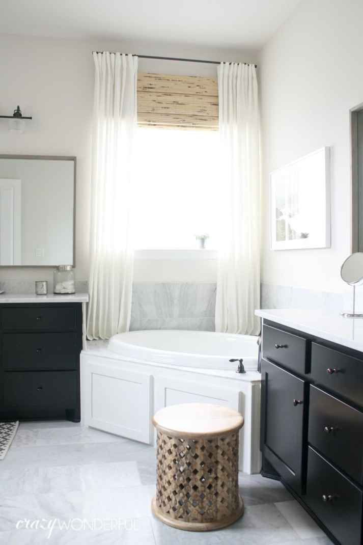 window behind corner bathtub covered with woven wood shades and white curtains