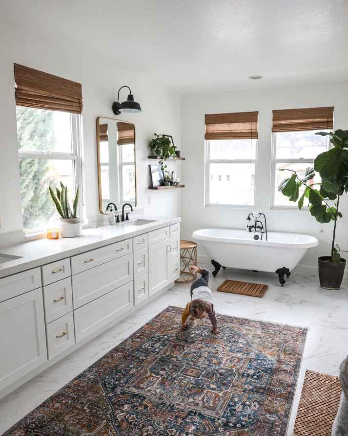 Large bathroom with white cabinets, concrete counters and brown woven shades on windows over clawfoot tub