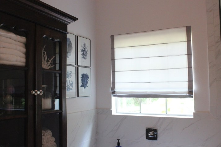 Natural light filtering through the Blinds.com roman shades in the master bathroom