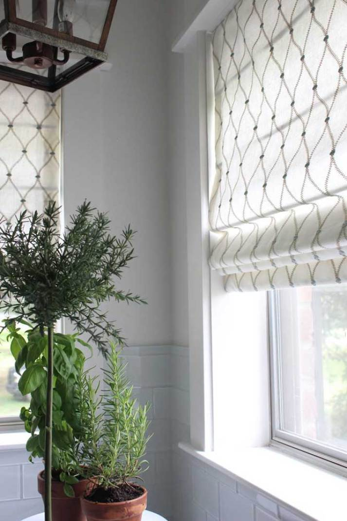 Close-up of Blinds.com roman shades installed in windows