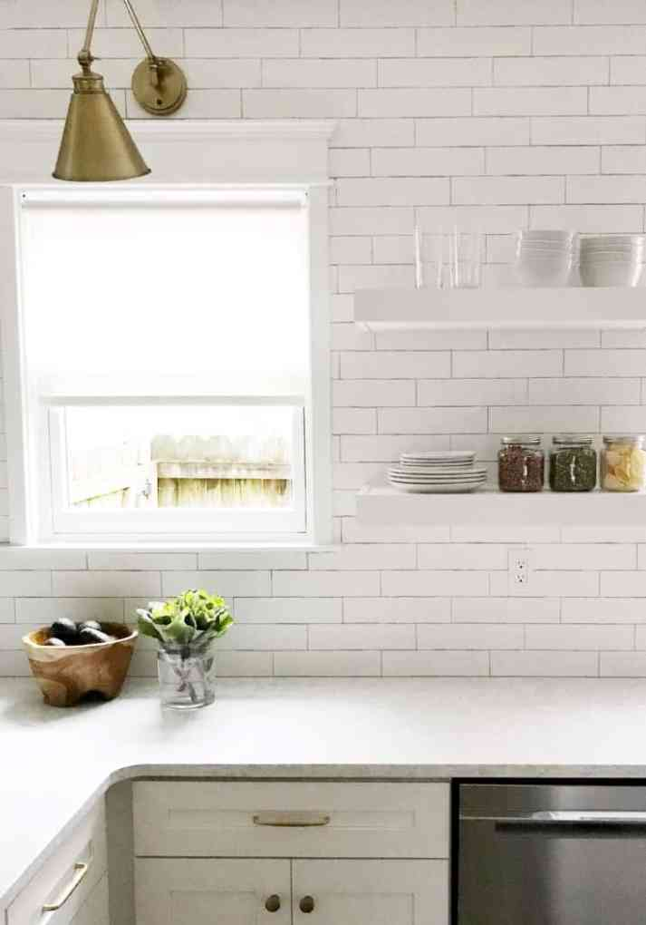 Close-up of kitchen white roller shades with brass sconce above window