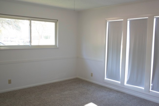 before image of empty guest bedroom with old white roller shades